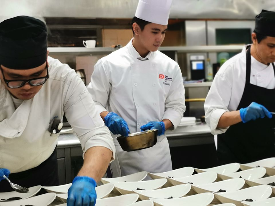 A culinary student prepares food while flanked by two chefs